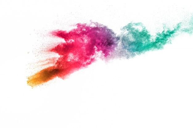 白い背景の上の抽象的なマルチカラー粉塵爆発。塵粒子スプラッシュの動きを凍結します。