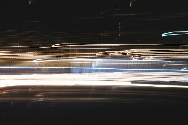 Abstract of multicolored city lights beams in motion, moving colorful lines or light painting led building abstraction on busy city light trails background. vertical desigh