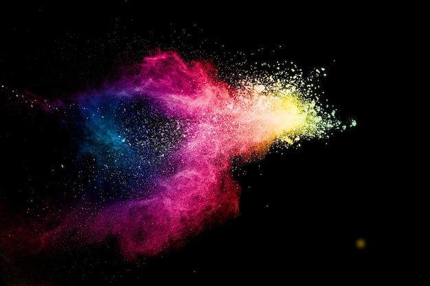Абстрактный разноцветный взрыв порошка на черном фоне.