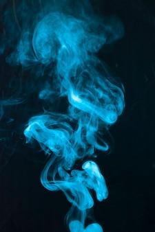 검은 배경에 위쪽으로 이동하는 푸른 연기 매연의 개요