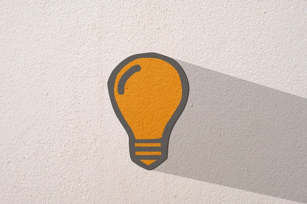 Abstract orange thinking light bulb on concrete wall background
