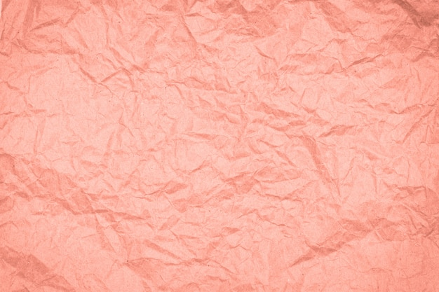 Abstract packaging craft wrinkled paper texture, background  toned in trendy color 2020 coral pink