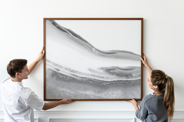 Abstract painting being hung by a couple