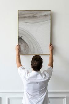 Abstract painting being hung by a young man on a white minimal wall
