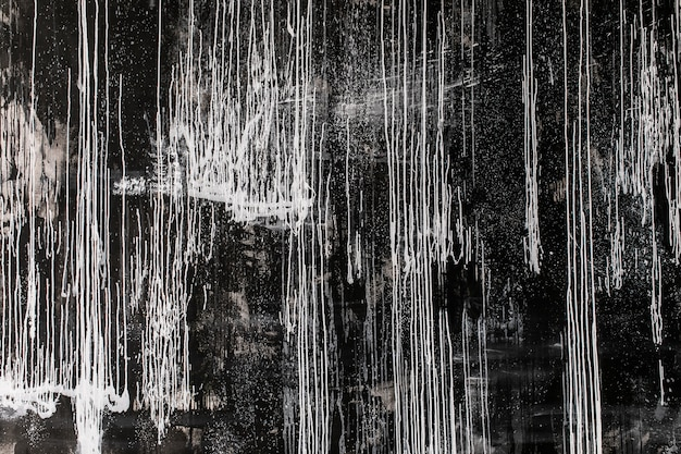 Abstract painting - smudges and splashes of white paint on a dark background