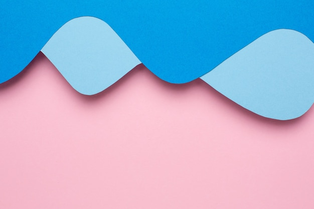Abstract paper cut blue waves art on pink