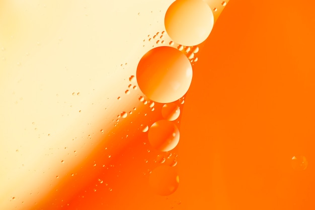 Abstract pattern of coloured oil bubbles on water