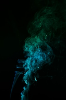 The abstract pattern made from blue and green smoke rising from an incense stick