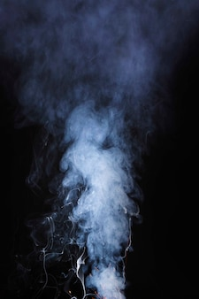 The abstract pattern made from smoke rising from an incense stick on black background