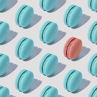그림자가 있는 흰색 배경에 파란색과 분홍색 마카롱이 있는 추상 패턴입니다. 완벽 한 패턴입니다. 맛있는 건강식 프랑스 디저트. 크리에이 티브 최소한의 현대적인 개념입니다.