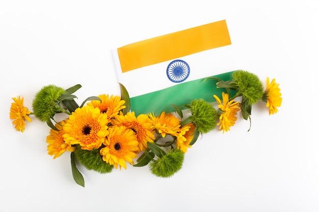 白い表面にオレンジと緑の花のフレームと抽象的なパターン。インド独立記念日のコンセプト