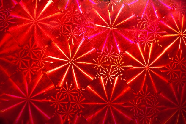 Abstract pattern with rays on red holographic paper.