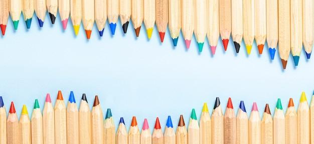 Абстрактная квартира карандаша лежала на синем панорамном фоне. скопируйте пространство. панорама баннер со школьными канцелярскими принадлежностями.
