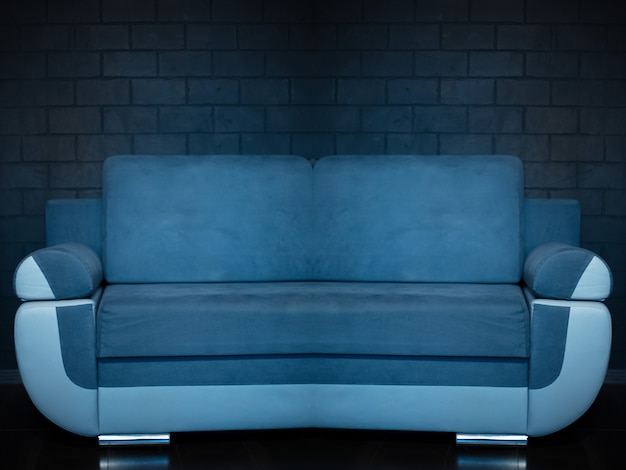 Abstract photo collage of blue sofa on background of black brick wall.