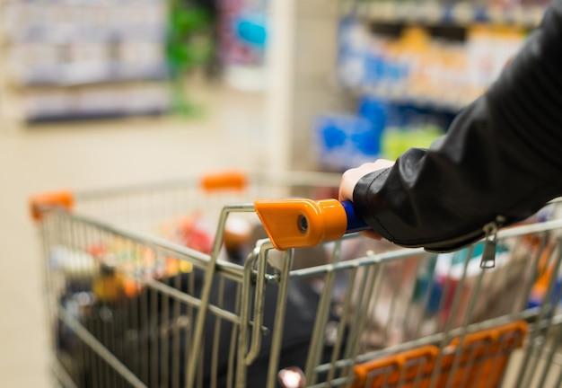 Абстрактное фото женщины, несущей тележку или тележку в супермаркете.