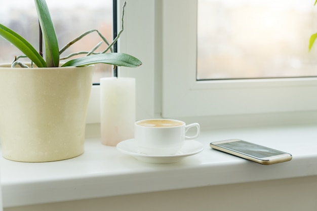 Abstract photo windowsill morning white cup with coffee mobile phone