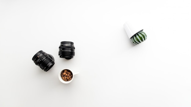 Abstract photo with camera lenses coffee and cactus plant sideways