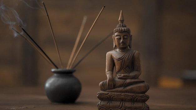 Abstract picture of a modern office in oriental style, selective focus on smoking incense sticks and wooden buddha figurine at table
