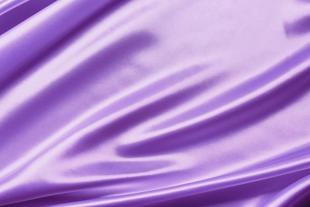 背景に抽象的な紫色のサテンの絹のような布、折り目波状の折り目が付いたファブリックテキスタイルドレープ。柔らかい波で、風に揺れています。