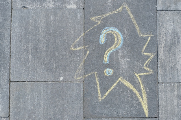 Abstract question mark drawn in crayons on gray asphalt