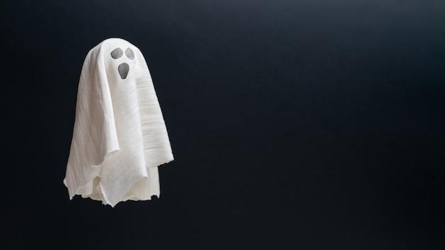 コピースペースで飛んでいる抽象的なぼろきれの幽霊。ハロウィーンの休日。