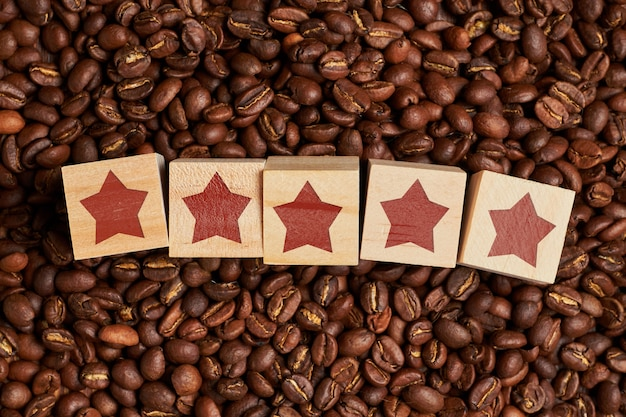 Abstract rating of five stars on wooden cubes on coffee beans. the concept of the best coffee.