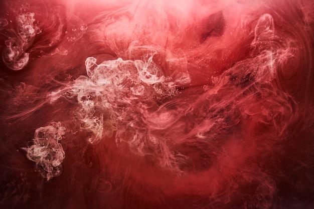 抽象的な赤い海の背景、水中のルビーの絵の具、鮮やかな明るい煙の緋色の壁紙