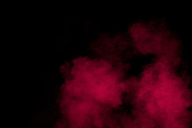 Взрыв пыли абстрактный красный порошок на черном фоне.