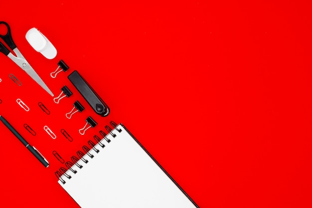 Abstract red table with stationary . blank notebook and scissors, pensils, pens. flatlay top horizontal view copyspace.