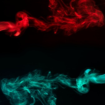 Abstract red and turquoise smoke on black dark background