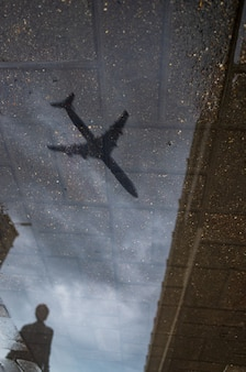 Abstract reflection of a city street in a rainy puddle flying airplane