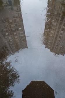 비오는 웅덩이에 있는 도시 거리의 추상적 반사가 우산 가장자리에 보입니다.