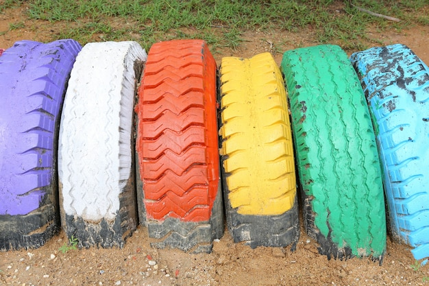 Abstract refused color painted tire heap on sand, modern recycling concept