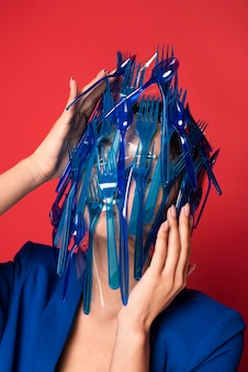 Abstract representation of blue plastic tableware waste on woman