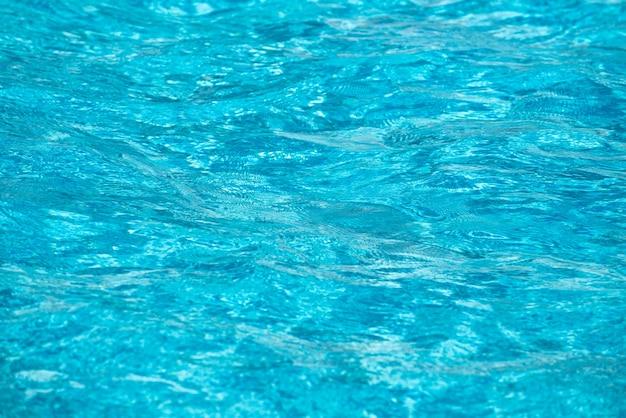 スイミングプールの抽象的な波紋と透明なターコイズブルーの水面、背景と抽象的なデザインの青い水波。
