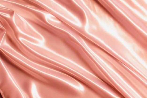 Абстрактная атласная шелковистая ткань из розового золота для фона, ткань текстильная драпировка со складками, волнистыми складками. с мягкими волнами, развевающимися на ветру.