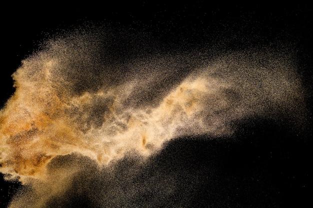 Abstract sand cloud. golden colored sand splash against dark background.