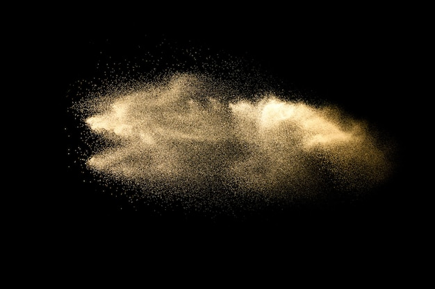 Abstract sand cloud.golden colored sand splash agianst dark background.yellow sand fly wave in the air.