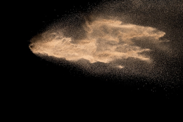 Abstract sand cloud. golden colored sand splash agianst dark background.