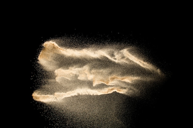 Abstract sand cloud.golden colored sand splash on dark