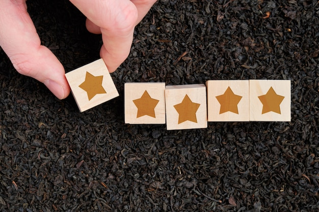 Abstract score, a rating of star wooden cubes holds a hand against the background of black tea.
