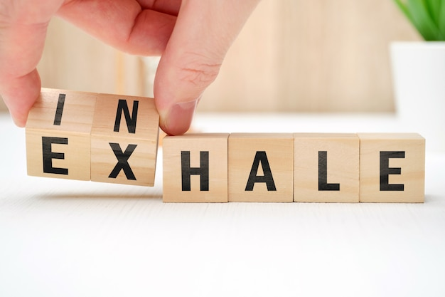 Abstract selection of inhale exhale phrases on wooden blocks.