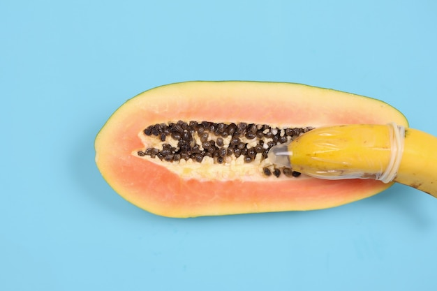 Abstract sexual health representation with banana and papaya isolated on blue background