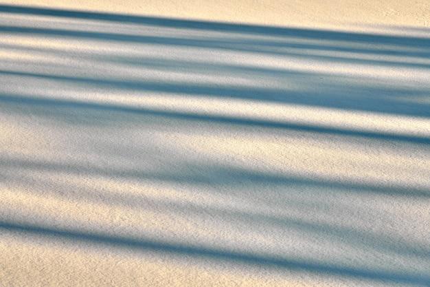 Абстрактные теневые линии на зимнем фоне снега. чистый снег, освещенный солнечным светом. пейзаж для открытки, плаката, баннера.