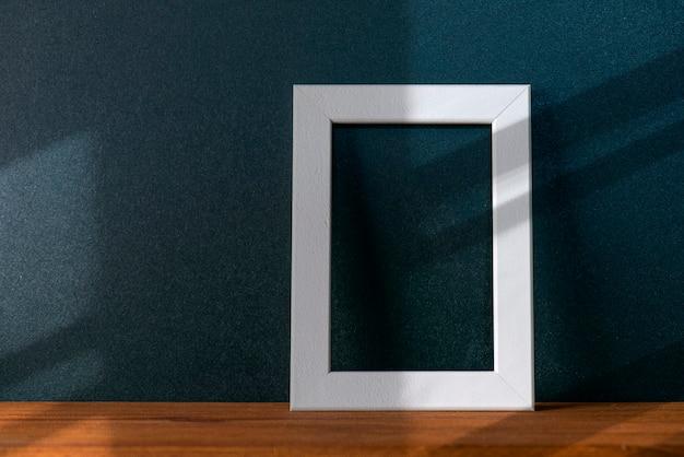 최소한의 인테리어가 있는 방의 검은 벽에 추상적인 선 그림자가 있습니다. 나무 테이블에 흰색 빈 사진 프레임이 있는 구성, 장식 모형, 텍스트 공간