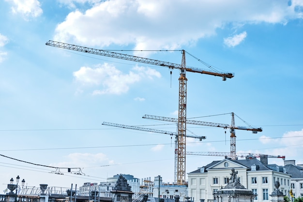 Abstract shape construction site with cranes at daylight