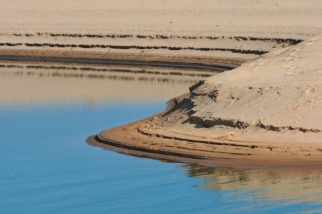 Abstract shapes on the shore of a lake with low water level