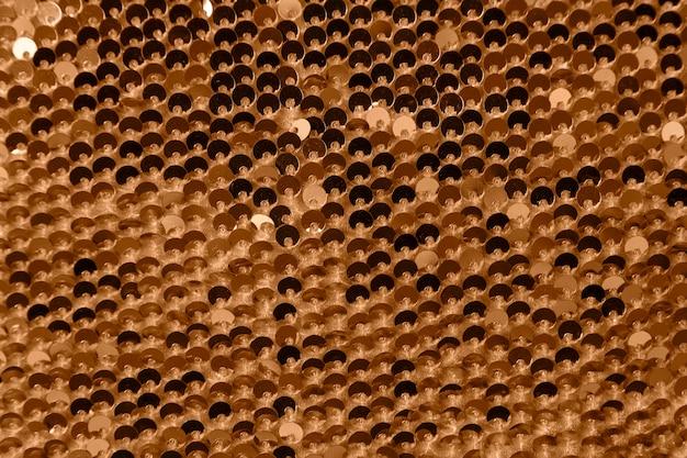 抽象的な光沢のある背景。ゴールドのスパンコールをあしらった生地。スパンコール。繊維。閉じる。