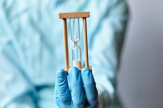 Абстрактное время знака уходит - врач в медицинских перчатках держит песочные часы.