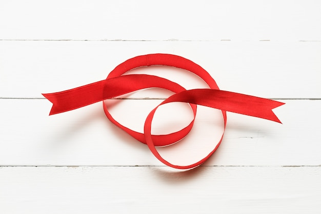 Abstract silk ribbon on white wooden background